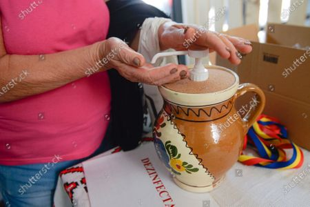 An elderly lady uses disinfectant packed in a traditional clay pot against the COVID-19 infection at the opening of a market selling Romanian food products discounted by 25 percent for pensioners and 15 percent for students living or studying in the district surrounding,in Bucharest, Romania, . Several community welfare investments were inaugurated in the recent weeks as Romania approaches the end of local elections electoral campaign, although the events were not officially related to the upcoming ballot on Sept. 27