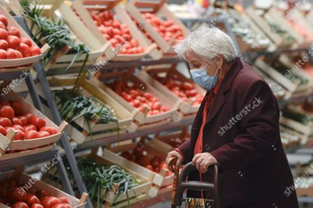 An elderly lady wearing a mask for protection against COVID-19 infection looks at vegetables after the opening of a market selling Romanian food products discounted by 25 percent for pensioners and 15 percent for students living or studying in the district surrounding,in Bucharest, Romania, . Several community welfare investments were inaugurated in the recent weeks as Romania approaches the end of local elections electoral campaign, although the events were not officially related to the upcoming ballot on Sept. 27