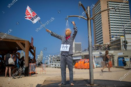 Protester wearing a mask of Prime Minister Benjamin Netanyahu showers during a protest against government's decision to close beaches during the three-week nationwide lockdown due to the coronavirus pandemic, in Tel Aviv, Israel, . Israel went back into a full lockdown on Friday to try to contain a coronavirus outbreak that has steadily worsened for months as its government has been plagued by indecision and infighting