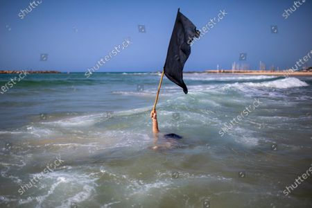 Stock Photo of Man waves a black flag in the water during a protest against government's decision to close beaches during the three-week nationwide lockdown due to the coronavirus pandemic,in Tel Aviv, Israel, . Israel went back into a full lockdown on Friday to try to contain a coronavirus outbreak that has steadily worsened for months as its government has been plagued by indecision and infighting