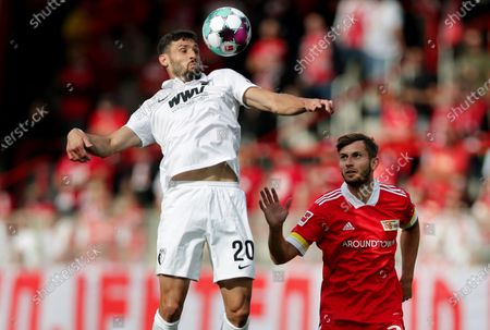 Stock Photo of Augsburg's Daniel Caligiuri, left, and Union's Christopher Lenz, right, challenge for the ball during the German Bundesliga soccer match between 1. FC Union Berlin and FC Augsburg in Berlin, Germany