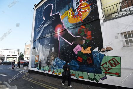A woman passes a mural dedicated to British musician George Michael near the site of his old home in Kingsbury in north London, Britain, 19 September 2020. Artist Dawn Mellor said it celebrates the singer as a pioneering cultural and LGBTQ+ figure. The artwork is in Kingsbury, north west London, where he lived and went to school.