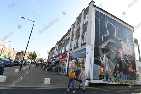 People pass a mural dedicated to British musician George Michael near the site of his old home in Kingsbury in north London, Britain, 19 September 2020. Artist Dawn Mellor said it celebrates the singer as a pioneering cultural and LGBTQ+ figure. The artwork is in Kingsbury, north west London, where he lived and went to school.