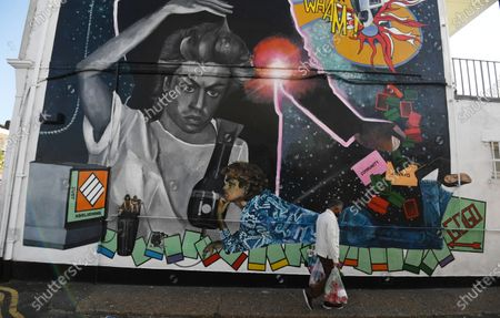 A man passes a mural dedicated to British musician George Michael near the site of his old home in Kingsbury in north London, Britain, 19 September 2020. Artist Dawn Mellor said it celebrates the singer as a pioneering cultural and LGBTQ+ figure. The artwork is in Kingsbury, north west London, where he lived and went to school.