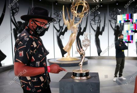 D-Nice known as Derrick Jones, a disc jockey, rapper producer, left, checks out the Emmy hand sanitizer dispenser during rehearsals Friday for the 72nd Annual Emmy Awards taking place at Staples Center this Sunday. Staples Center on Friday, Sept. 18, 2020 in Los Angeles, CA. (Al Seib / Los Angeles Times