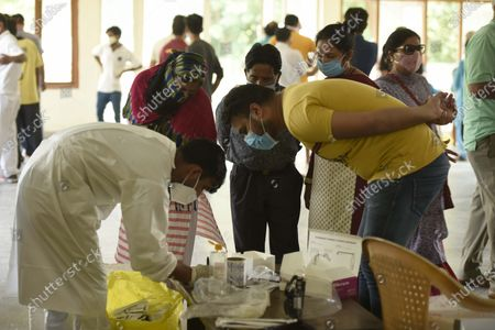 A health worker wearing PPE coveralls registers people for coronavirus test at the Community Centre in Sector-15 part-2 near Huda Market, on September 19, 2020  in Gurugram, India.