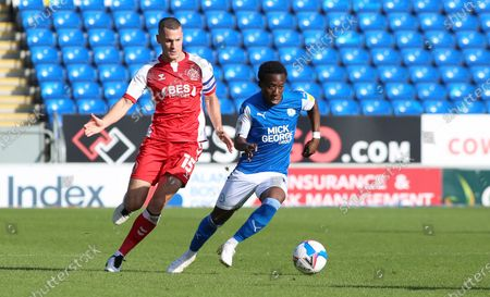 Siriki Dembele of Peterborough United in action with Paul Coutts of Fleetwood Town