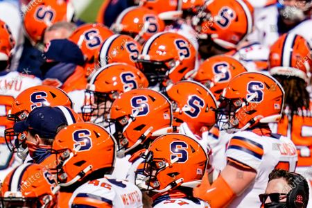 The Syracuse football team gathers on the field to warm up before an NCAA college football game against Pittsburgh, in Pittsburgh