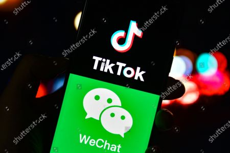 Stock Image of In this photo illustration the TikTok and WeChat logos are seen displayed on a smartphone.