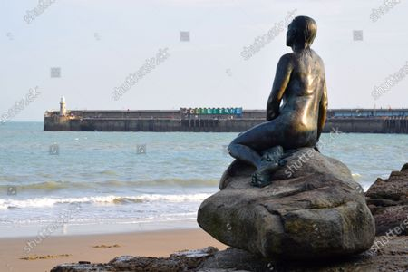 The Kent seaside town of Folkestone early evening. Image shows The Folkestone Mermaid by Cornelia Parker, forever gazing out to sea, across Sunny Sands beach.