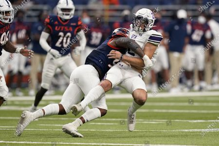 Stephen F. Austin quarterback Trae Self, right, is hit and stopped by UTSA defensive lineman Lorenzo Dantzler, left, during the second half of an NCAA college football game, in San Antonio