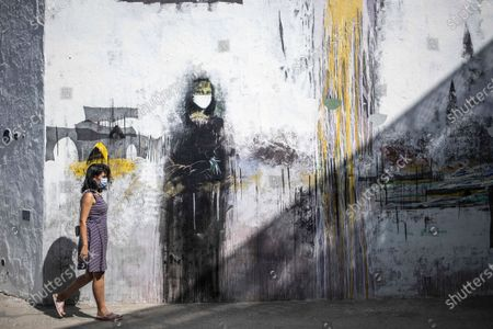Woman wearing a face mask to prevent the spread of coronavirus walks past a mural of a mask-wearing Mona Lisa, in the Medina of Asilah, northern Morocco, . The town is known for its well-preserved ramparts which were built by the Portuguese in the 15th century and is nowadays a hub for street art and cultural events