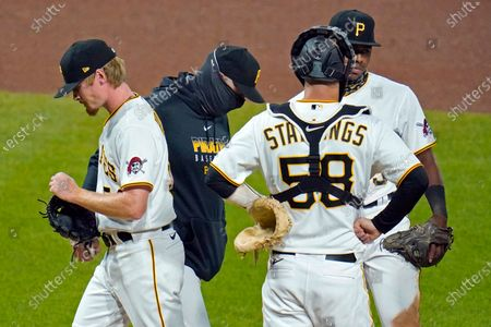 Pittsburgh Pirates relief pitcher Sam Howard, left, walks off the mound after handing the ball to manager Derek Shelton, second from left, during the seventh inning of the team's baseball game against the St. Louis Cardinals in Pittsburgh