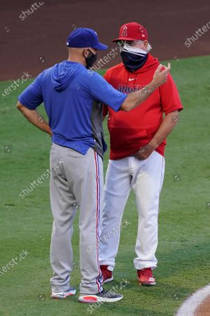 Texas Rangers manager Chris Woodward, left, talks with Los Angeles Angels manager Joe Madden before a baseball game, in Anaheim, Calif
