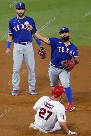 Los Angeles Angels' Mike Trout slides after being forced out at second, while Texas Rangers second baseman Rougned Odor throws to first after a grounder by Los Angeles Angels' Anthony Rendon, who was out at first during the eighth inning of a baseball game, in Anaheim, Calif