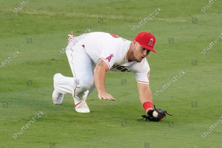 Los Angeles Angels center fielder Mike Trout reaches to catch a ball hit by Texas Rangers' Isiah Kiner-Falefa for an out during the first inning of a baseball game, in Anaheim, Calif