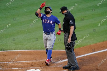 Texas Rangers' Rougned Odor, left, crosses home plate after hitting a home run during the first inning of a baseball game against the Los Angeles Angels, in Anaheim, Calif. Rangers' Nick Solak also scored due to the home run