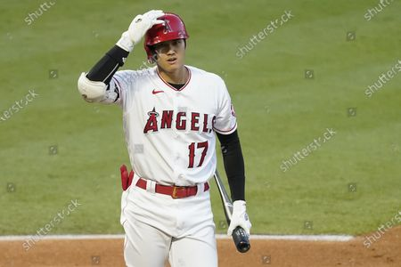 Los Angeles Angels designated hitter Shohei Ohtani adjusts his helmet before batting during the second inning of a baseball game against the Texas Rangers, in Anaheim, Calif