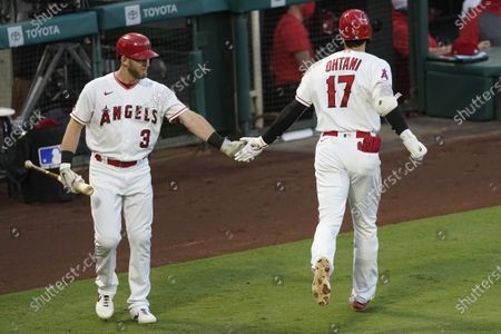 Los Angeles Angels designated hitter Shohei Ohtani, right, celebrates hitting a solo home run with Taylor Ward during the second inning of a baseball game against the Texas Rangers, in Anaheim, Calif