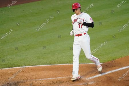 Los Angeles Angels designated hitter Shohei Ohtani crosses home plate after hitting a solo home run during the second inning of a baseball game against the Texas Rangers, in Anaheim, Calif