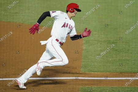 Los Angeles Angels designated hitter Shohei Ohtani runs to home base to score after a double by Taylor Ward during the fifth inning of a baseball game against the Texas Rangers, in Anaheim, Calif