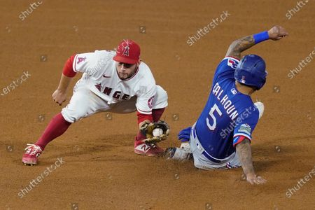Texas Rangers designated hitter Willie Calhoun, right, makes it to second base ahead of a tag by Los Angeles Angels second baseman David Fletcher after a wild pitch by Andrew Heaney during the fourth inning of a baseball game, in Anaheim, Calif
