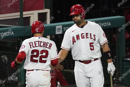 Los Angeles Angels' David Fletcher, left, celebrates with Albert Pujols after scoring off a single by Mike Trout during the ninth inning of a baseball game against the Texas Rangers, in Anaheim, Calif
