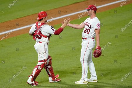 Los Angeles Angels catcher Max Stassi and relief pitcher Mike Mayers celebrate a win over the Texas Rangers in a baseball game, in Anaheim, Calif