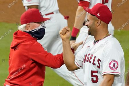 Los Angeles Angels manager Joe Madden, left, celebrates a win with Albert Pujols after a baseball game against the Texas Rangers, in Anaheim, Calif
