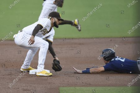 Seattle Mariners' Dylan Moore (25) steals second base past the tag of San Diego Padres shortstop Fernando Tatis Jr. (23) during the first inning of a baseball game, in San Diego