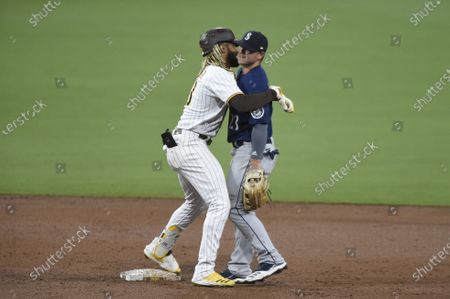 San Diego Padres' Fernando Tatis Jr. (23) hugs Seattle Mariners shortstop Dylan Moore (25) after hitting a double during the third inning of a baseball game, in San Diego