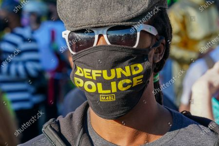 A protester wears a face mask written on Defund Police during a Black Trans Lives Matter rally in Hudson River Park.