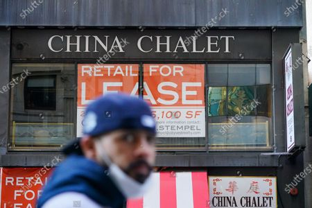 A pedestrian wearing a face mask walks past the China Chalet, the Financial District establishment that was a Chinese restaurant by day and party spot by night which has closed permanently.