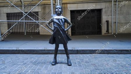 Stock Picture of The Fearless Girl dressed with the iconic neck collar of the former Supreme Court Justice Ruth Bader Ginsburg as a tribute to her at Wall Street. Ginsburg died at 87 at her home in Washington, D.C surrounded by family on September 18, 2020.