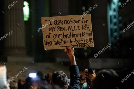 Stock Photo of A sign is held in the air with a Ruth Bader Ginsburg quote during a vigil held at the NY Supreme Court on September 20, 2020 in New York, NY. Ruth Bader Ginsburg served as an associate justice on the Supreme Court from 1993 until her death on September 18, 2020.