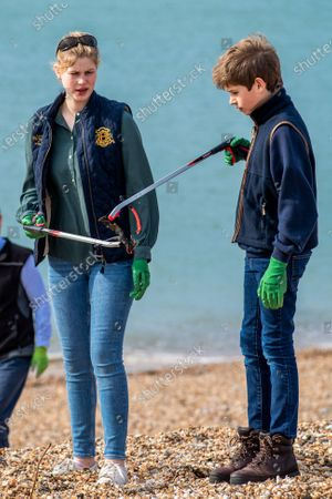 James Viscount Severn and Lady Louise Windsor collecting rubbish on the beach