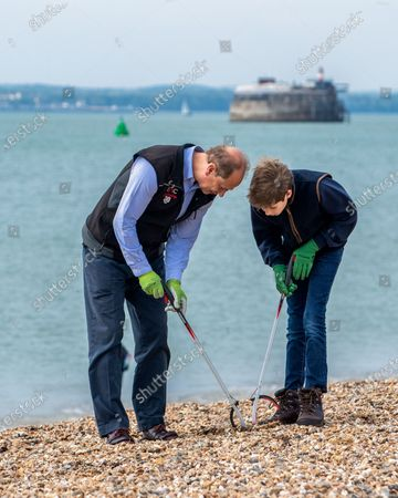Prince Edward and James Viscount Severn collecting rubbish on the beach