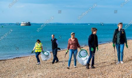 Stock Image of Prince Edward, Sophie Countess of Wessex and James Viscount Severn collecting rubbish on the beach