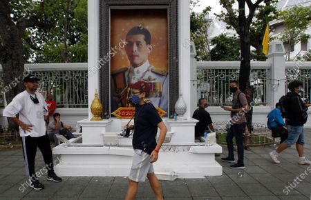 Anti-government protesters walks past a portrait of Thailand's King Maha Vajiralongkorn during the demonstration at the Sanam Luang. Pro-democracy protesters converged at the historic royal heart of Bangkok to demand the resignation of the military-backed government and reforms of the monarchy, long considered a taboo subject in Thailand. The demonstrators gathered first at the Thammasat university campus on a college football field that was the scene of a massacre of left-wing students by pro-regime paramilitaries in 1976.