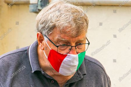 A pederstrian wearing a facemaks printed with tge Italian national colours. Italy was considered one of the safer holiday destinations for Brits and has remained on the travel corridor list since it first came about. But does this spike mean Italy is going on the UK quarantine list?