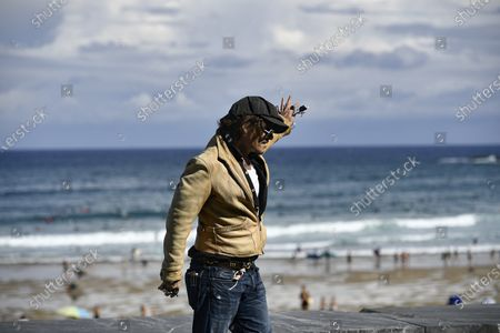 """Actor and film producer Johnny Deep, waves fans while standing along the beach during the photocall to promote his film """"Crock of Gold: A Few Rounds with Shane Macgoman"""" at the 68th San Sebastian Film Festival, in San Sebastian, northern Spain"""