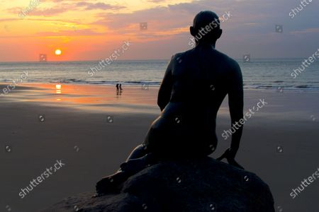 The Kent seaside town of Folkestone Sunrise.Image shows The Folkestone Mermaid by Cornelia Parker, forever gazing out to sea, across Sunny Sands beach.