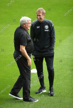 Newcastle United manager Steve Bruce, left, and Brighton manager Graham Potter talk before the English Premier League soccer match between Newcastle United and Brighton at St. James' Park in Newcastle, England