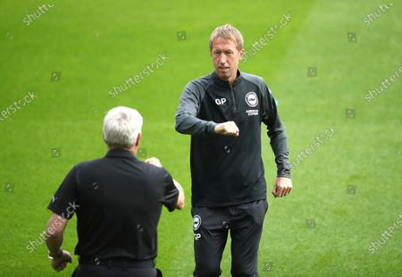 Newcastle United manager Steve Bruce, left, and Brighton manager Graham Potter bump elbows prior to the English Premier League soccer match between Newcastle United and Brighton at St. James' Park in Newcastle, England
