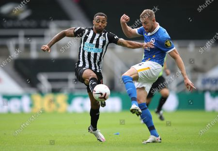 Newcastle's Callum Wilson, left, duels for the ball with Brighton's Adam Webster during the English Premier League soccer match between Newcastle United and Brighton at St. James' Park in Newcastle, England