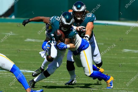 Philadelphia Eagles running back Boston Scott (35) breaks from Los Angeles Rams defensive end Morgan Fox (97) as Eagles teammate center Jason Kelce (62) pressures during the first quarter of an NFL football game, in Philadelphia