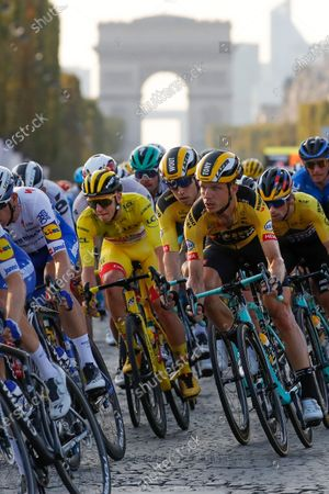 Slovenia's Tadej Pogacar, wearing the overall leader's yellow jersey, center, rides down Champs Elysees with Germany's Tony Martin, third from right, and Slovenia's Primoz Roglic, second right, in the pack as the Arc de Triomphe is seen in the background during the twenty-first and last stage of the Tour de France cycling race over 122 kilometers (75.8 miles), from Mantes-la-Jolie to Paris, France