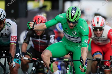 Sam Bennett of Ireland, wearing the best sprinter's green jersey celebrates as he crosses the finish line to win the twenty-first and last stage of the Tour de France cycling race over 122 kilometers (75.8 miles), from Mantes-la-Jolie to Paris, France, . Left is third place Slovakia's Peter Sagan