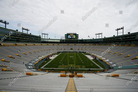 Stock Image of Players begin to warm up as the seats are empty at Lambeau Field before an NFL football game between the Green Bay Packers and the Detroit Lions, in Green Bay, Wis