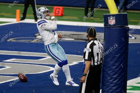 Dallas Cowboys quarterback Dak Prescott (4) celebrates running the ball for a touchdown as back judge Greg Meyer (78) looks on in the second half of an NFL football game against the Atlanta Falcons in Arlington, Texas